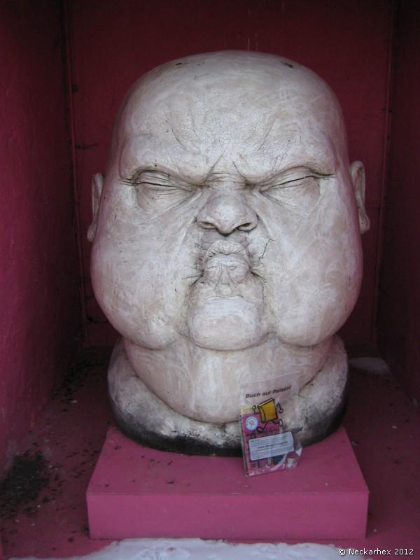 �berlebensgrosse Skulptur eines Kopfes in einem aufgegebenen Trafoh�uschen